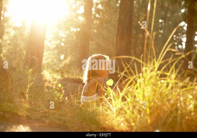 Girl sitting in forest with warm sun - Stock-Bilder