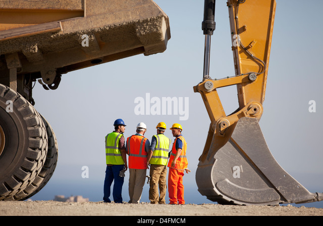 Workers talking by machinery in quarry - Stock Image