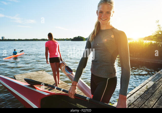 Fit woman with a kayak getting ready for practice - Stock Image