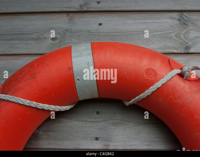 Lifebelt hanging on a wooden shed - Stock Image