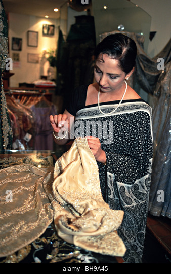 UK Indian fashion designer stitching a sari in her shop in Wembley, London - Stock Image