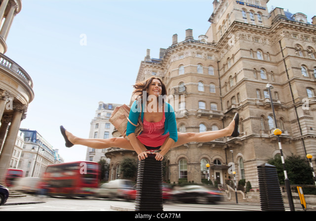 Mid adult woman in pink dress leapfrogging through city street - Stock Image