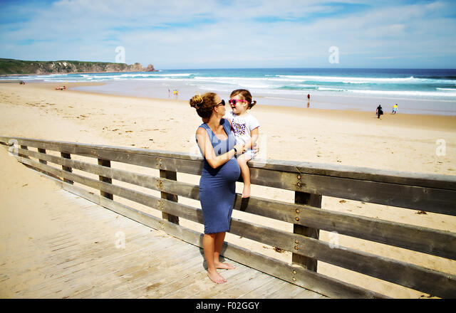 Pregnant woman at beach with her daughter - Stock Image
