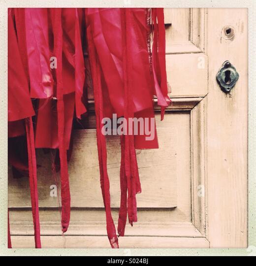 Red costume on old wooden door - Stock Image