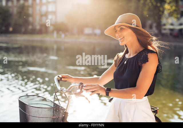 Image of beautiful woman with a bicycle at summer time near the pond at park. Female model wearing hat looking away - Stock Image