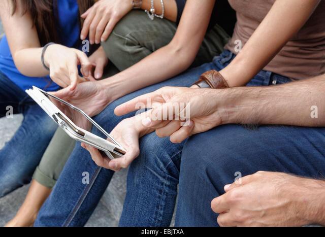 Group of friends looking at digital tablet, focus on tablet and hands - Stock Image