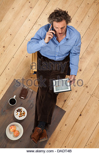 Overhead view of male on mobile phone in studio space - Stock Image