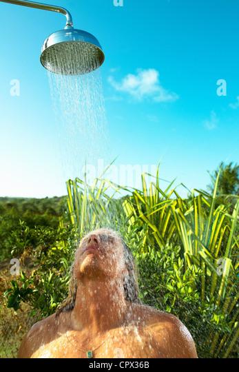 Man enjoying cool shower outdoors - Stock-Bilder