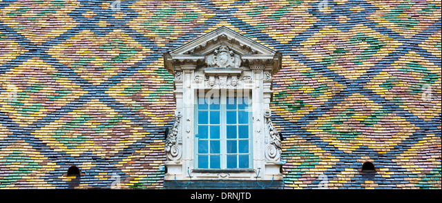 Traditional polychrome roof tiles of Hotel de Vogue in Rue de la Chouette in Dijon in the Burgundy region of France - Stock Image