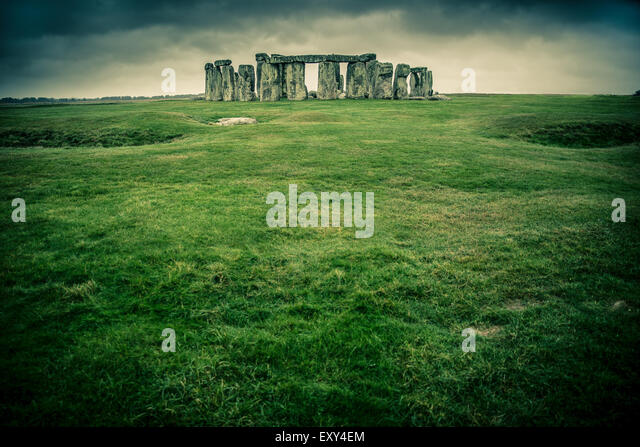 Grass field leading to Stonehenge on a cloudy gray day - Stock Image