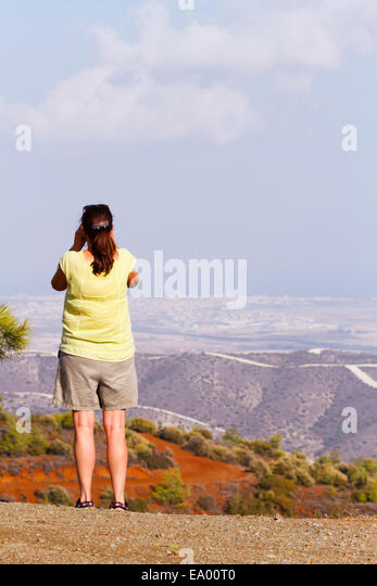 Woman tourist takes in the veiw overlooking Larnaca from Stavrovouni, Cyprus - Stock Image