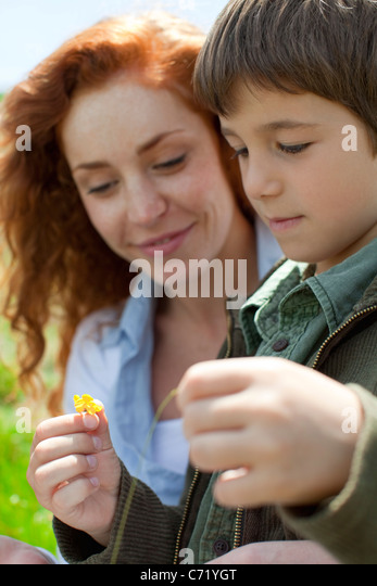 Boy looking at flower outdoors with his mother - Stock Image