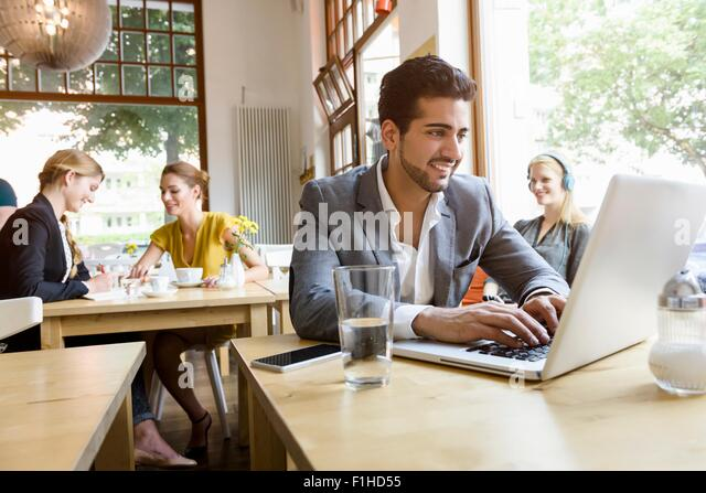 Young man using laptop in cafe - Stock-Bilder