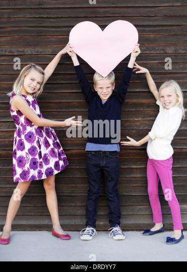 Siblings holding up large paper heart - Stock-Bilder
