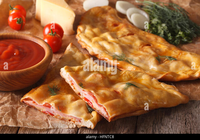 Cut Italian pizza calzone with ham and cheese close-up on the table and ingredients. horizontal - Stock Image