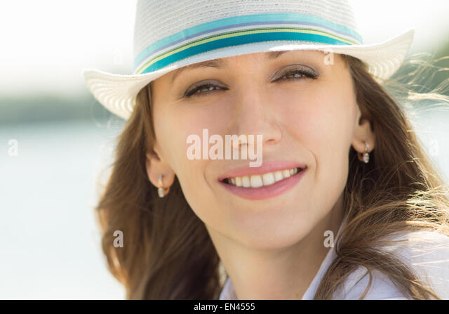 Young beautiful woman in white hat at the summer day. Pretty caucasian girl has fun on vacation - Stock-Bilder