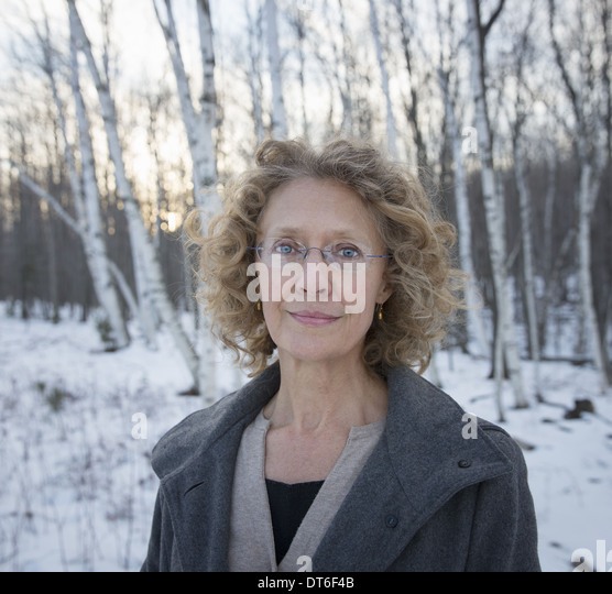 A mature woman with curly read hair, wearing a coat. Standing on a snowy path through woodland. - Stock Image