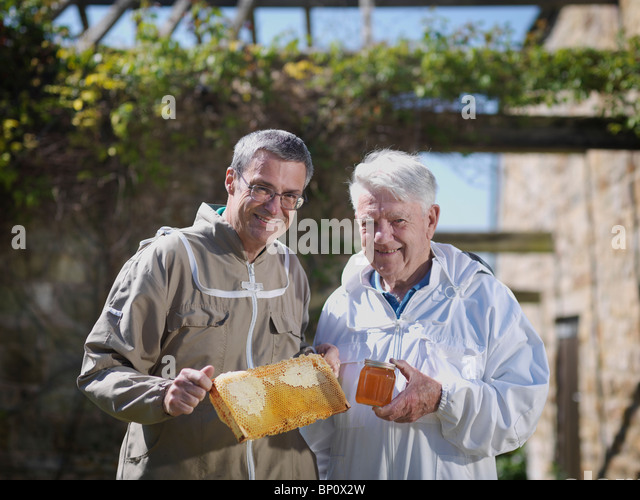 Beekeepers with honey comb and honey - Stock Image