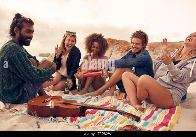 Group of young friends celebrating at a beach party together. Young people having new year celebration at the seaside. - Stock Image