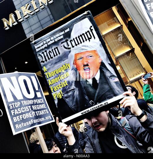 E 57th St, New York, New York, USA. 11th Jan, 2017. A protester holds up a banner outside Trump Tower in New York - Stock Image