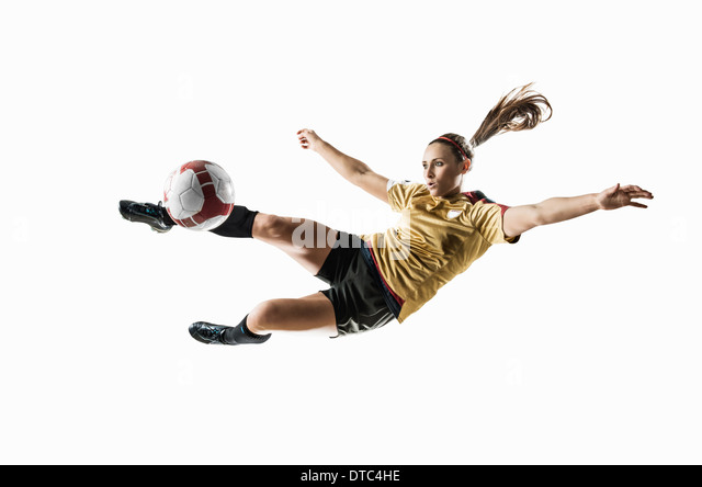 Studio shot of young female soccer player kicking ball mid air - Stock Image
