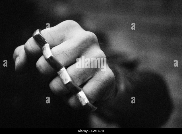 Hand with brass knuckles, close-up, b&w - Stock Image