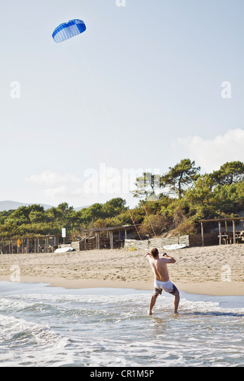 Man flying kite on beach - Stock Image