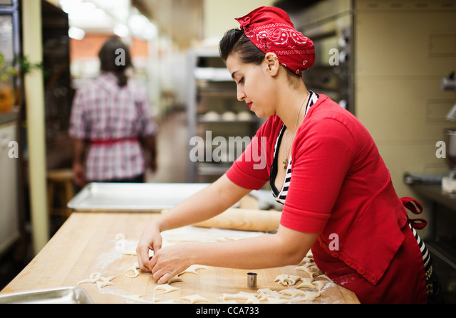 Young baker preparing food in kitchen - Stock-Bilder
