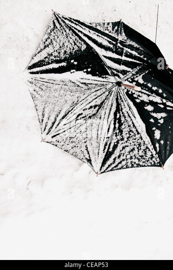 Broken umbrella in snow - Stock Image