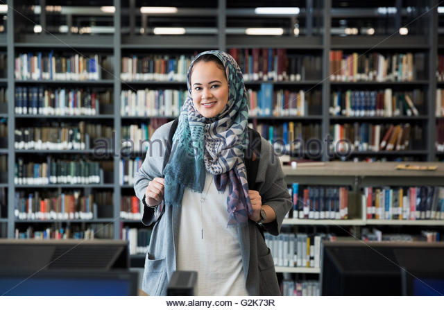 Portrait smiling college student wearing hijab in library - Stock-Bilder