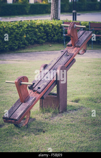 Old wood seesaw in childhood illustrating nostalgic concept. - Stock Image