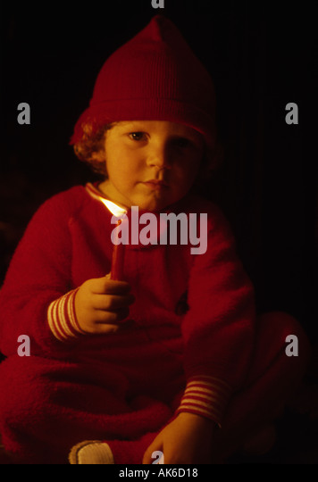 Santas helper hold a lighted candle in the dark of Christmas Eve - Stock Image