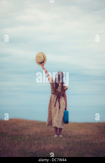 a girl in a vintage dress with suitcase holding a hat - Stock Image