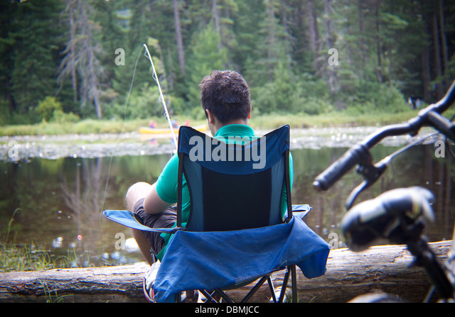 A teenage boy fishing by the lakeside in his camp chair - Stock Image