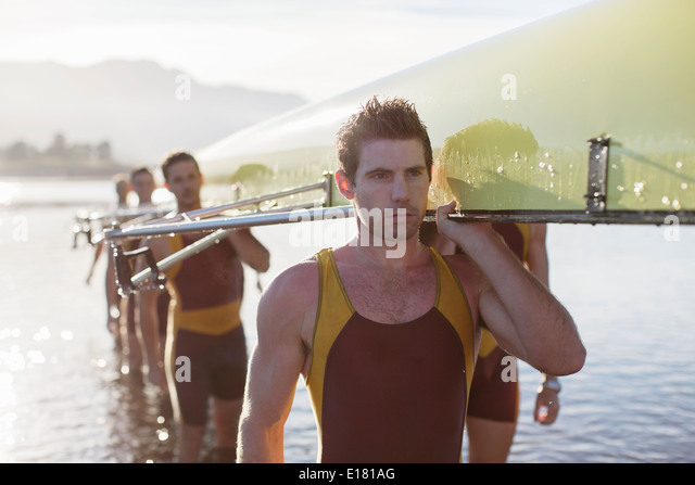 Rowing team carrying scull out of lake - Stock Image