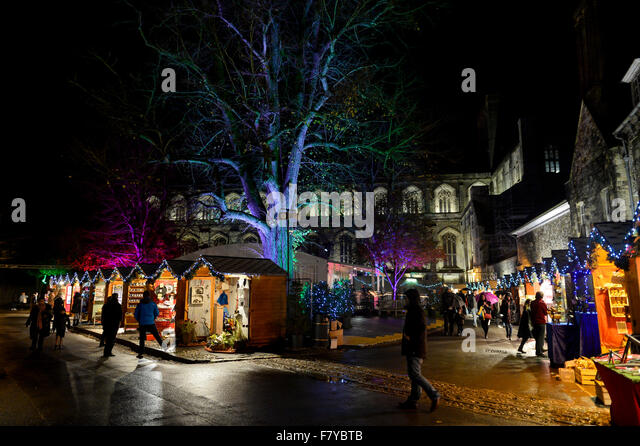 Winchester Christmas Market, Hampshire UK. Stalls of the annual Christmas market light up the grounds of Winchester - Stock Image