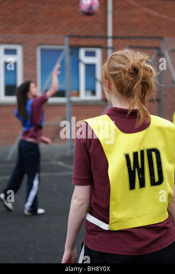 Teenage girls playing netball, physical education, PE, sports and games lesson,  secondary school, Wales UK - Stock Image