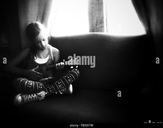Girl Playing Ukulele In House - Stock Image