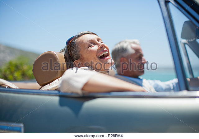 Mature couple driving in convertible - Stock Image