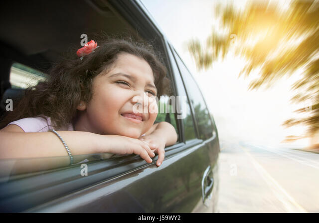 Smiling girl looking out car window - Stock Image