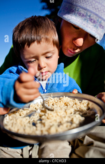 a boy sits on his mothers lap while they eat noodles in the backcountry. They are camped at Squaw Pass. - Stock-Bilder