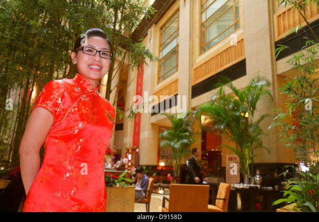 Singapore Singapore River Boat Quay The Fullerton Hotel lobby atrium Asian woman uniform employee smiling inside - Stock Image