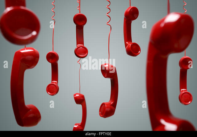 Red telephone receiver hanging - Stock Image