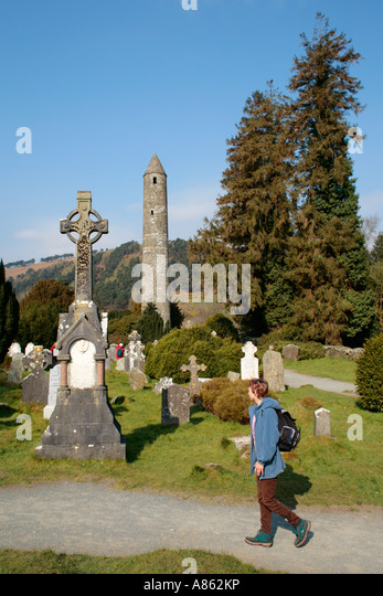 round tower and tombstones at Glendalough in County Wicklow in Ireland - Stock Image