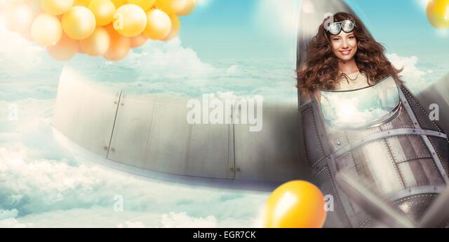Fantasy. Happy Woman in Cockpit of Aircraft Having Fun - Stock Image