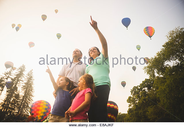 Mid adult couple and two daughters looking up and pointing at hot air balloons at festival - Stock-Bilder