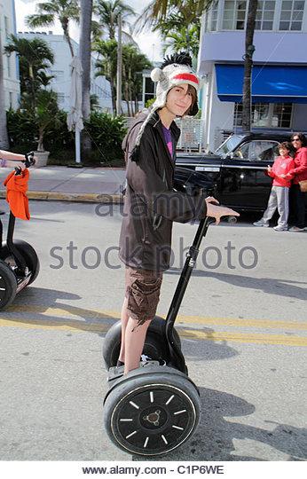 Miami Beach Florida Ocean Drive teen boy male Segway - Stock Image