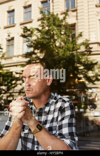 Sweden, Man sitting with hands clasped - Stock Image
