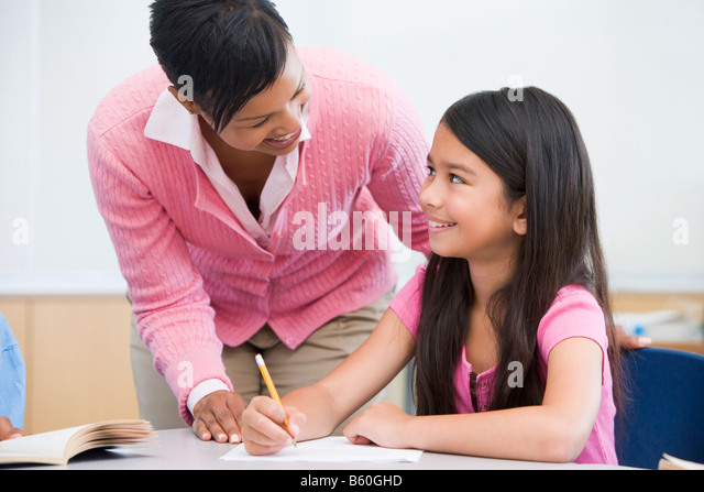 Student in class writing with teacher - Stock Image