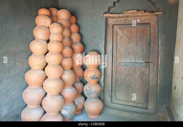Potter's house porch, wooden front door and piles of clay pots stacked against the wall, near Rayagada, Orissa, - Stock Image